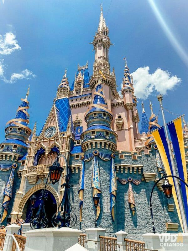 Castelo da Cinderela na Disney. Ele tem detalhes de laços azuis e dourados nas suas torres e nas laterais para o aniversário de 50 anos.