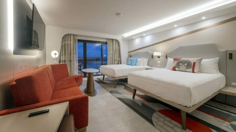 Imagem dos quartos temáticos dos Incríveis no hotel Contemporary. Há duas camas com lençóis brancos e um sofá vermelho.