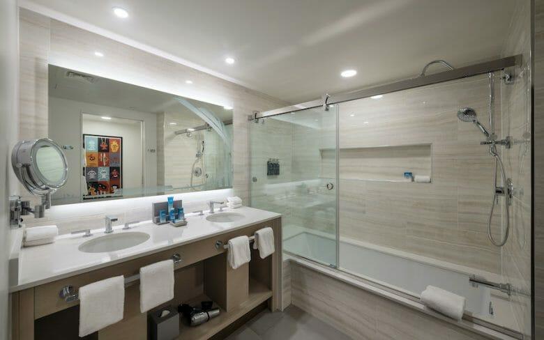 O banheiro é em tons claros, tem duas pias, um espelhão e um chuveiro com banheira.