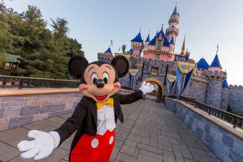 Mickey de roupa clássica e braços abertos em frente ao castelo da Disneyland California