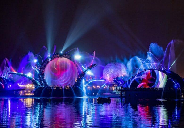 Foto de divulgação das luzes do HarmonioUS, o novo show noturno do Epcot, sobre o lago e com a Spaceship Earth ao fundo, em tons de azul, roxo e rosa