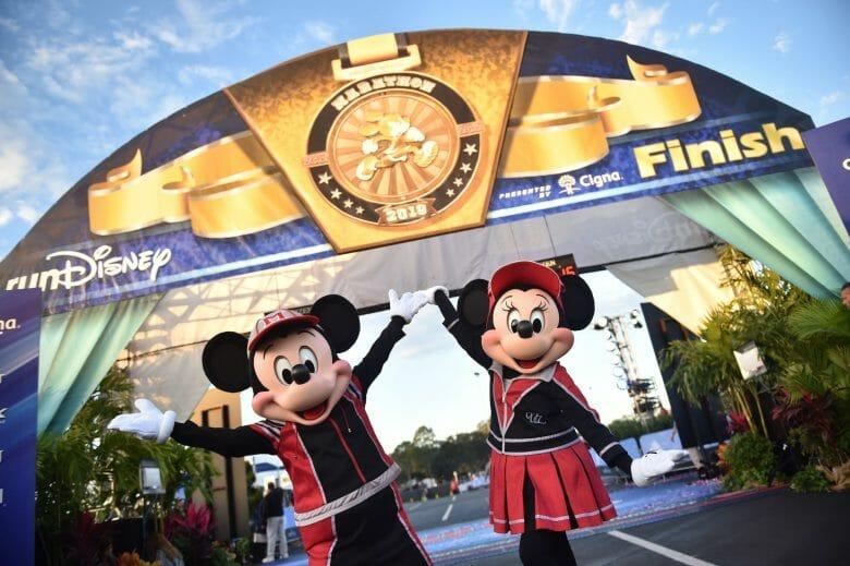 Mickey e Minnie com roupas de corrida em frente à chegada da corrida da Disney na maratona de 2019