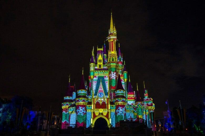 Foto do castelo da Cinderela no Magic Kingdom iluminado por projeções coloridas, com o céu noturno ao fundo.