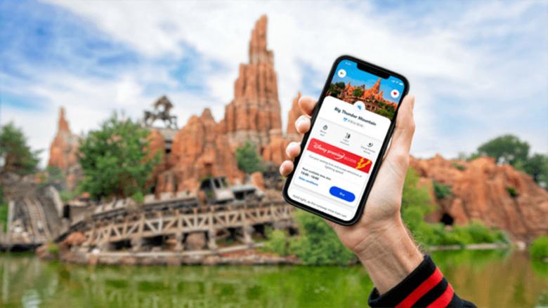 Uma mão segurando um celular com o Disney Premier Access na tela e a Splash Mountain ao fundo.