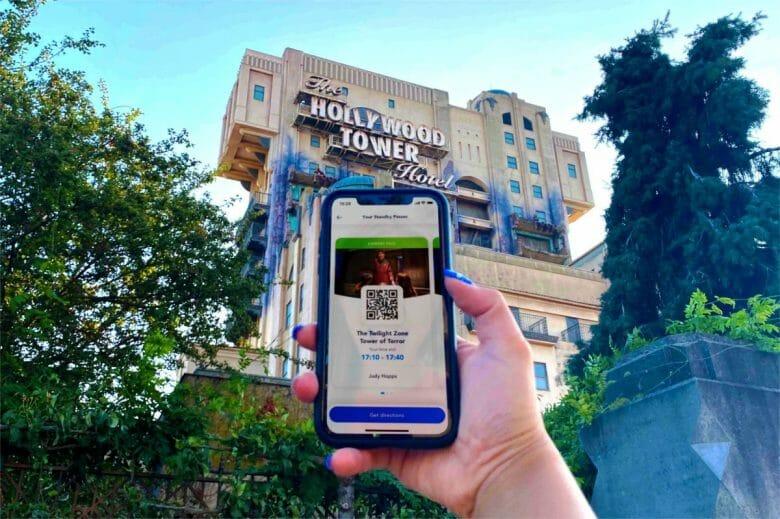 Uma mão segurando um celular   com o Standby Pass na tela e a Hollywood Tower ao fundo