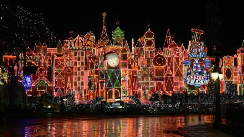 Fachada do It's A Small World com luzes natalinas em vermelho com detalhes em laranja e verde.