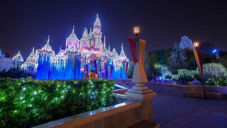 Castelo da Disneyland iluminado para o Natal em tons de branco, lilás e azul.
