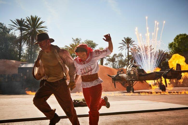 Imagem de dois atores durante o show do Indiana Jones, com um avião soltando fagulhas atrás