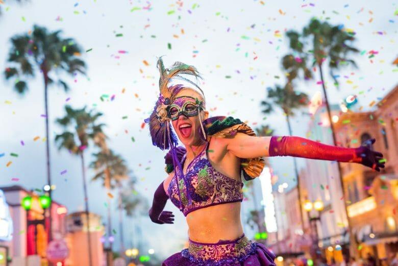 Foto de uma mulher de máscara de carnaval e roupa roxa na parada temática do Mardi Gras da Universal.